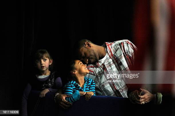 Paige Damiana 5 watches as Neveah Boone 5 nuzzles with her dad Marco a manufactur technician engineer for UQM as they wait for Vice President Joe...