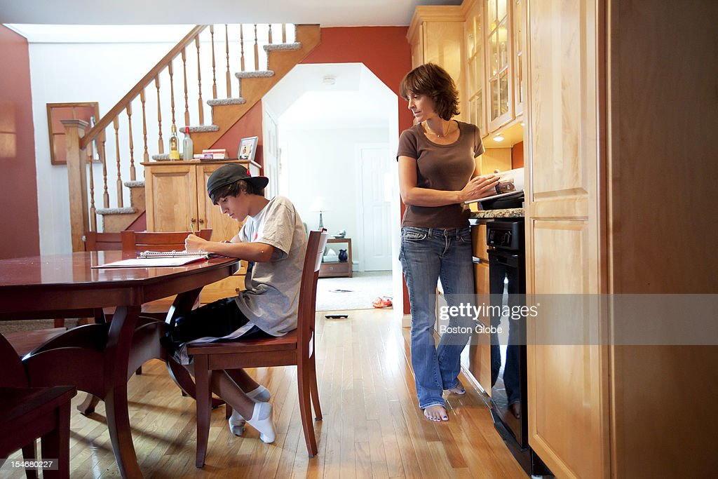 Paige Duncan watches her son Zach, 13, in the 8th grade, do his English Language Arts homework.