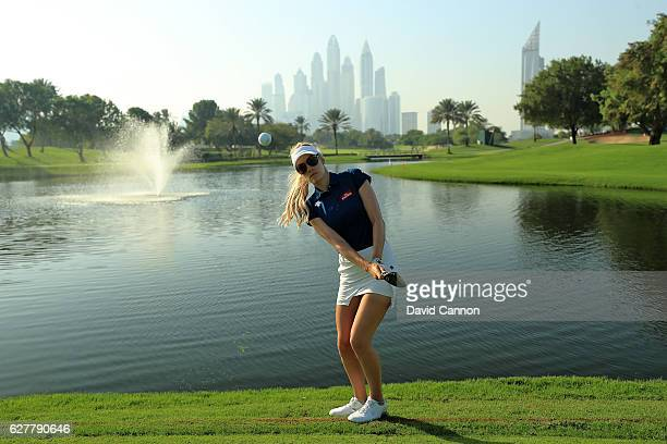 Paige Spiranac of the United States chips to the camera beside the fourth green during her practice round as a preview for the 2016 Omega Dubai...