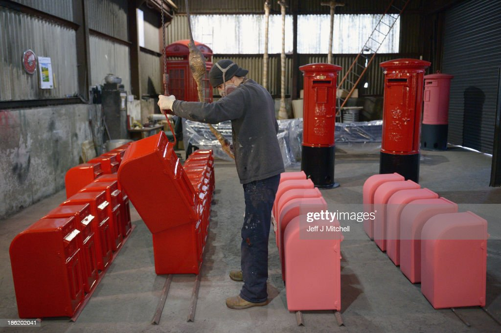 Pail Ainslie uses a spray gun as he paints a post box manufactured for the Royal Mail Group Ltd, in the paint workshop at Machan Engineering on October 29, 2013 in Denny, Scotland. The Royal Mail was privatized earlier this month with shares priced at 330p but then rose by more than 50%, which has encouraged critics to accuse the government of selling off Royal Mail too cheaply.