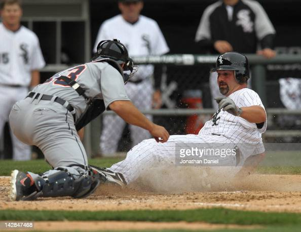 Pail Konerko of the Chicago White Sox beats the tag by Alex Avila of the Detroit Tigers to score a run in the 6th inning during the opening day game...