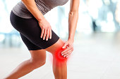 Portrait of sporty woman holding her injured knee after fitness workout. Red colouring spot has been added on the skin to demonstrate where the pain resides.