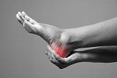 Pain in the foot. Massage of female feet. Pain in the human body on a gray background. Black and white photo with red dot