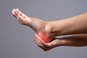 Pain in the foot. Massage of female feet. Pain in the human body on a gray background with red dot