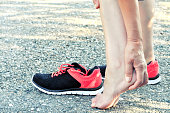 Pain in the foot.Running injury leg accident- sport woman runner hurting massaging painful sprained ankle in pain.Athlete woman has heel injury, sprained ankle during running training.
