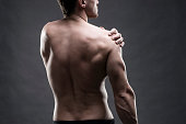 Pain in the shoulder. Muscular male body. Handsome bodybuilder posing on gray background. Low key close up studio shot. Middle part of the body