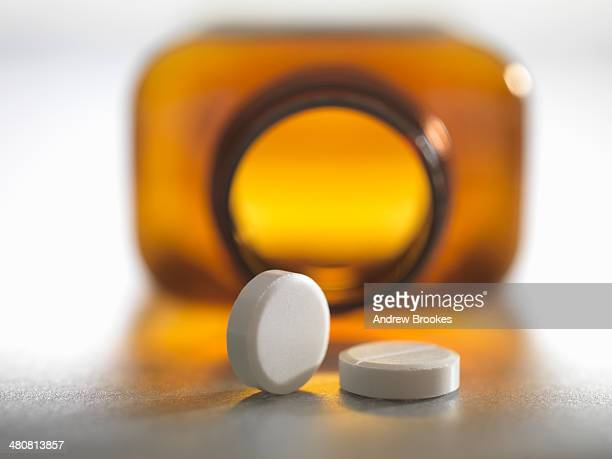 Pain killers pouring from brown medicine bottle