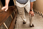 Senior adult having knee pain while climbing up stairs