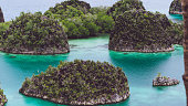 Painemo, Group of small island in shallow blue lagoon water, Raja Ampat, West Papua, Indonesia.