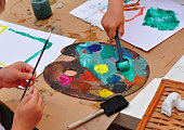 Children are painting, using Art Palette with paints , paintbrushes and rolls in their hands.