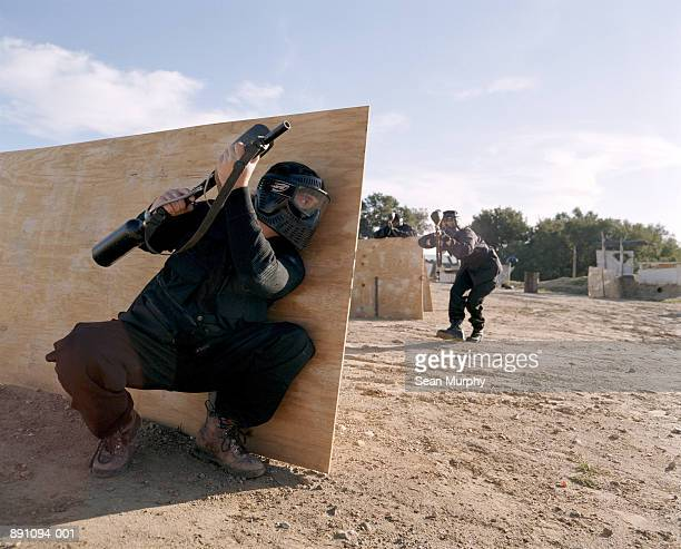 Paint ball battle, man hiding behind board, enemy attacking