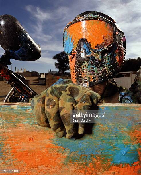 Paint ball player in camouflage wearing helmet covered in paint