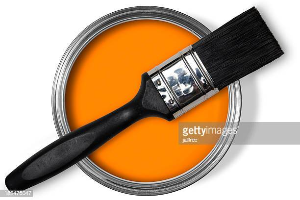 Paint brush sitting on tin of bright orange paint