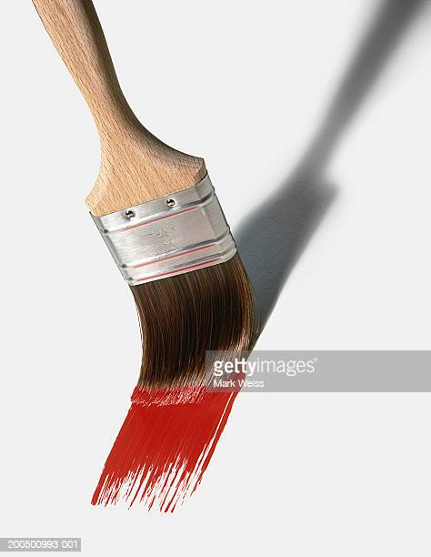 Paint brush spreading red paint