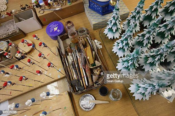 Paint brushes glue and paint jars stand next to painted wooden Christmas tree decorations drying at the worktable of an artisan at the Richard...