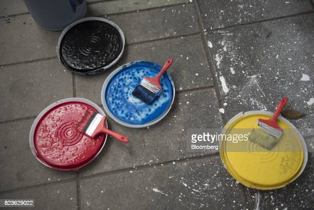Paint brushes sit in paint in the colors of the Venezuelan Flag while a progovernment supporter not pictured paints a mural on a wall at Andres Bello...