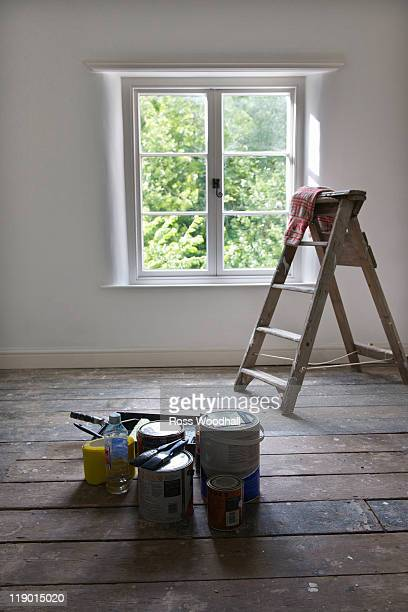 Paint cans and ladder in empty house