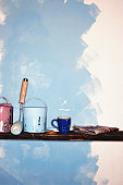 Paint cans, roller, mug and newspaper by partially painted wall