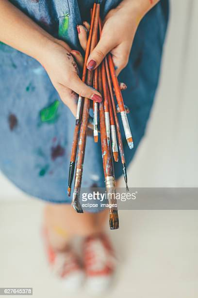 Paint covered hands of an artist holding paitnbrushes