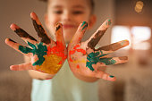 Hands covered in tempura paint. Focus is on hands.