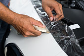 Installing paint protection film on white car