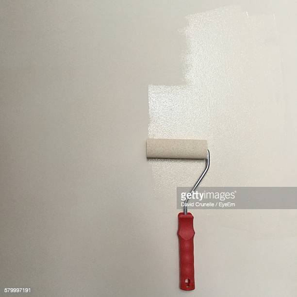 Paint Roller On Partially Painted Wall