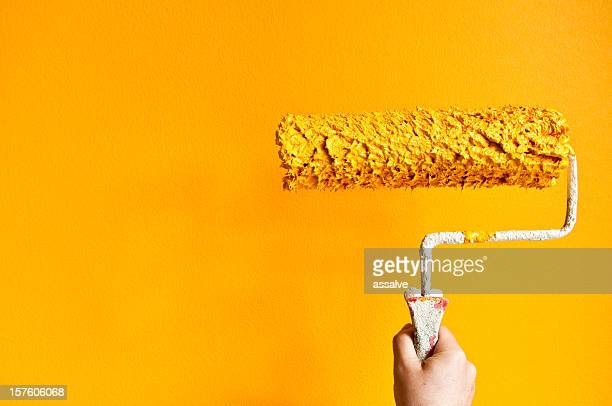 paint roller with orange color in front of colored wall
