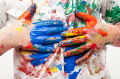 Paint soiled hands being wiped on a white shirt