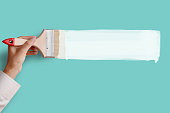 Man's hand holding paintbrush paint white color on blue aqua color wall, blank space for your text, banner, copyspace, advertising, or your design.