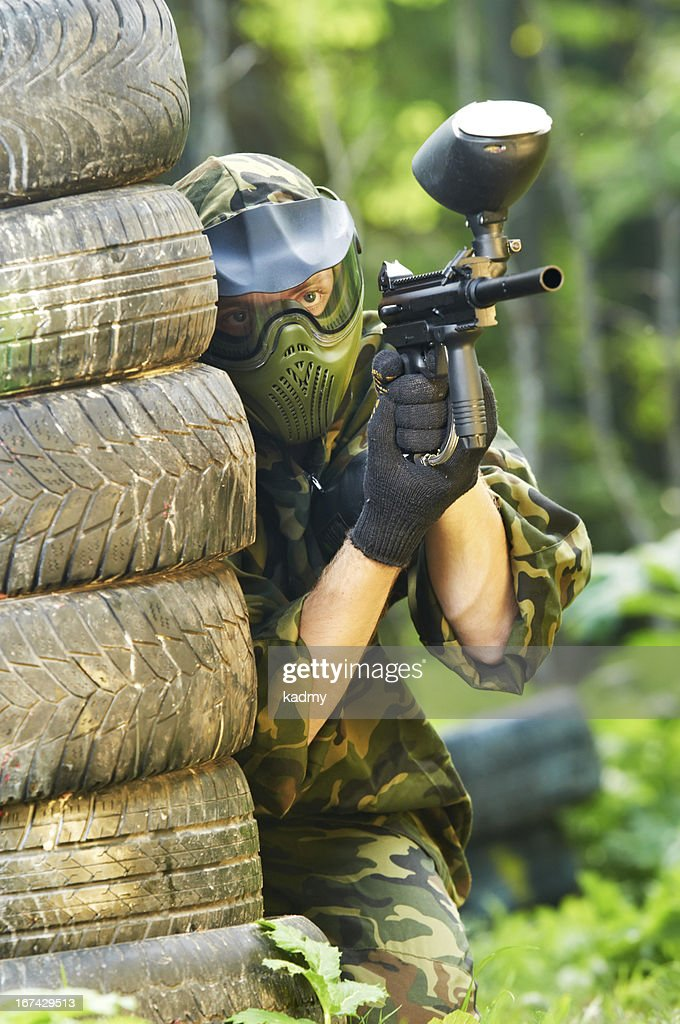 paintball player holding fire : Stock Photo