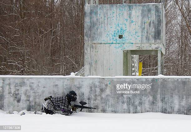 Paintballer crawling in snow by bunker