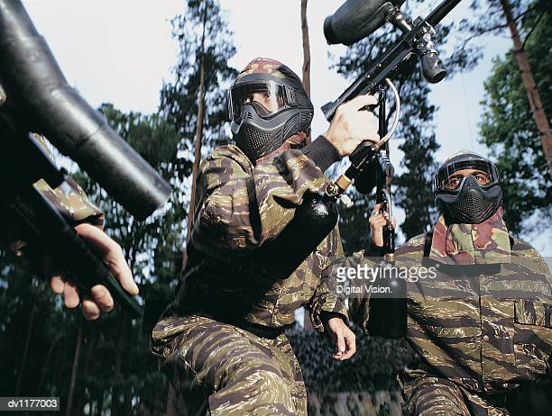Paintballers Holding Guns in a Forest