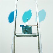 Paintbrush and can on ladder in front of three shades of blue on wall
