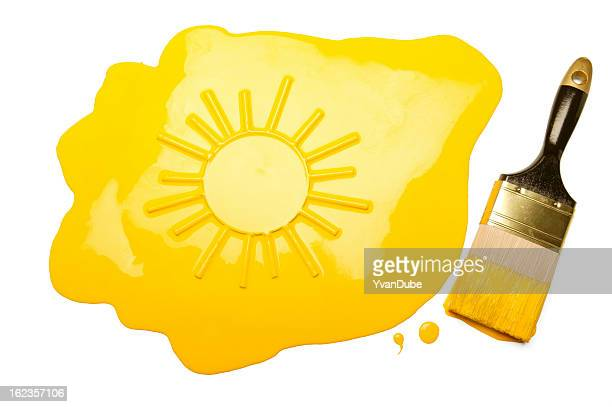 paintbrush and sun shape reflection in yellow paint blob