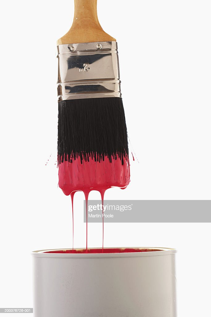 Paintbrush dripping red paint into paint can, close-up