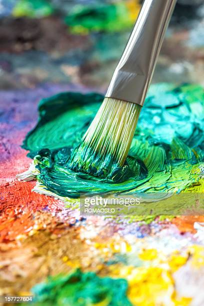 Pinsel mit grünen Ölfarbe auf einer klassischen Farbpalette