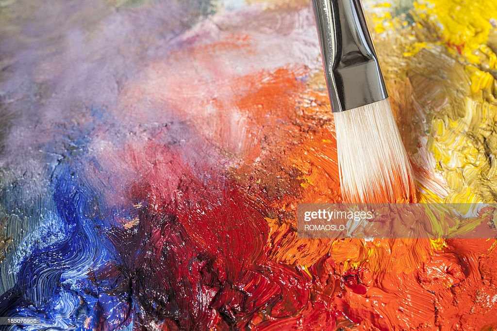 Paintbrush with red oil paint on a classical palette
