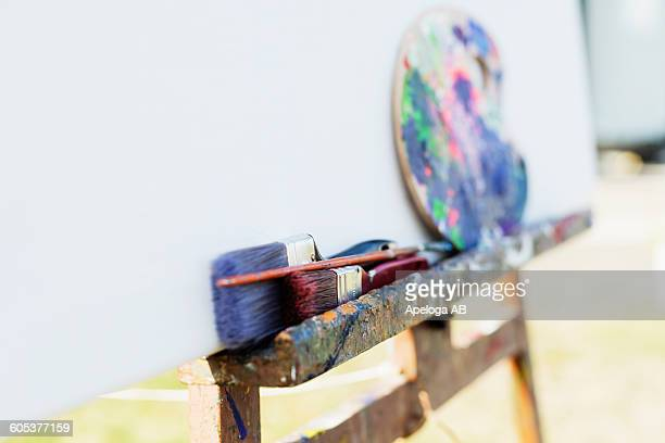 Paintbrushes and palette on easel outside studio