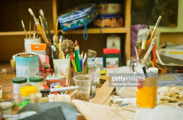 Paintbrushes, pencils and art tools on studio desk