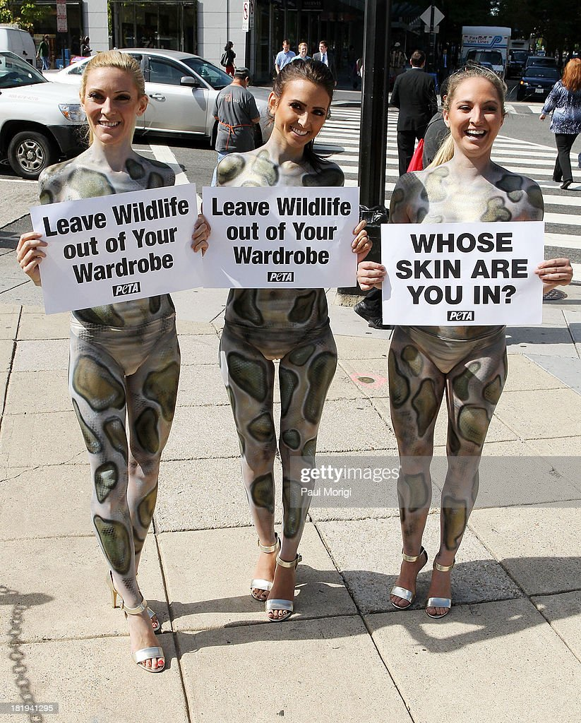 Painted as pythons PETA members (L to R) Ashley, Mary and Katie encourage passersby to leave wildlife out of their wardrobes during the PETA Save Our Skin protest at Farragut Square Park on September 26, 2013 in Washington, DC.