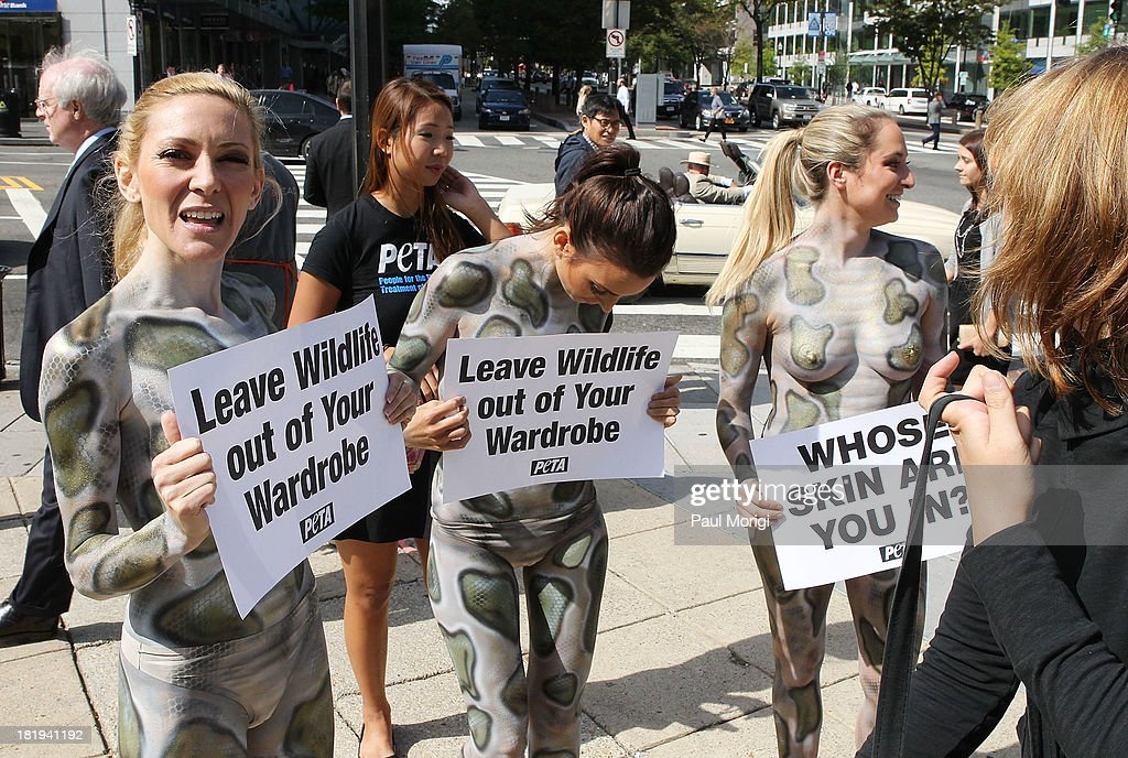 Painted as pythons PETA members encourage passersby to leave wildlife out of their wardrobes during the PETA Save Our Skin protest at Farragut Square Park on September 26, 2013 in Washington, DC.