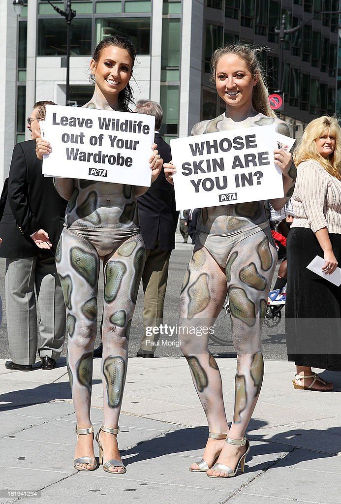 Painted as pythons PETA members Mary (L) and Katie encourage passersby to leave wildlife out of their wardrobes during the PETA Save Our Skin protest at Farragut Square Park on September 26, 2013 in Washington, DC.