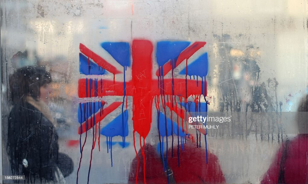 A painted British union flag is seen as people wait at a bus stop on the loyalist Shankill road in Belfast, Northern Ireland on December 12, 2012. Tensions have risen in the British province since councillors voted on December 3 to limit the number of days the Union Jack can fly over the City Hall to 17, outraging loyalists who believe Northern Ireland should retain strong links to Britain.