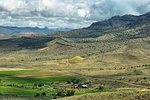 View of a ranch and mountains from Carroll rim trail in Painted Hills National Monument in Oregon, USA