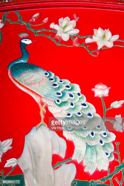 Painted jade peacock on a colourful decorative piece of Chinese furniture Xi'an China