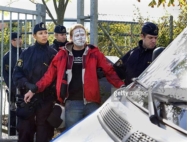 A painted peace activist is arrested by police at the rifle scope manufacturer Aimpoint factory in Malmo on September 19 2008 Some 70 participants in...