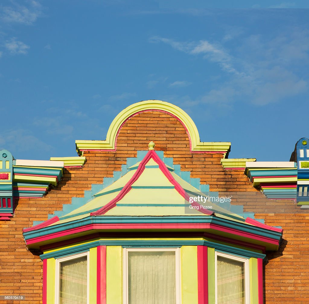 Painted row house pediment and bay window : Stock Photo