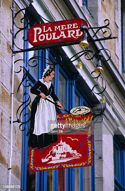 A painted sign, depicting a woman cooking over an open fire, over the entrance to La Mere Poulard, a restaurant famous for omelettes