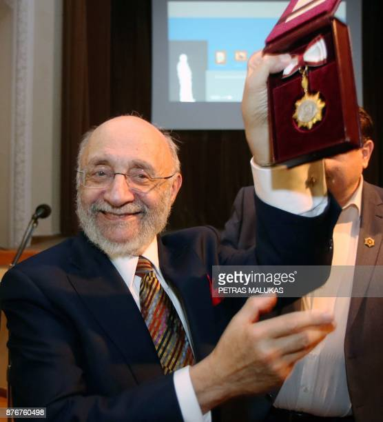Painter and Holocaust survivor Samuel Bak holds up a medal during the opening museum of his allegorical work inspired by Jewish history in the...