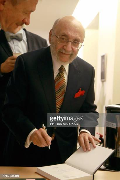 Painter and Holocaust survivor Samuel Bak signs a book during the opening museum of his allegorical work inspired by Jewish history in the Lithuanian...